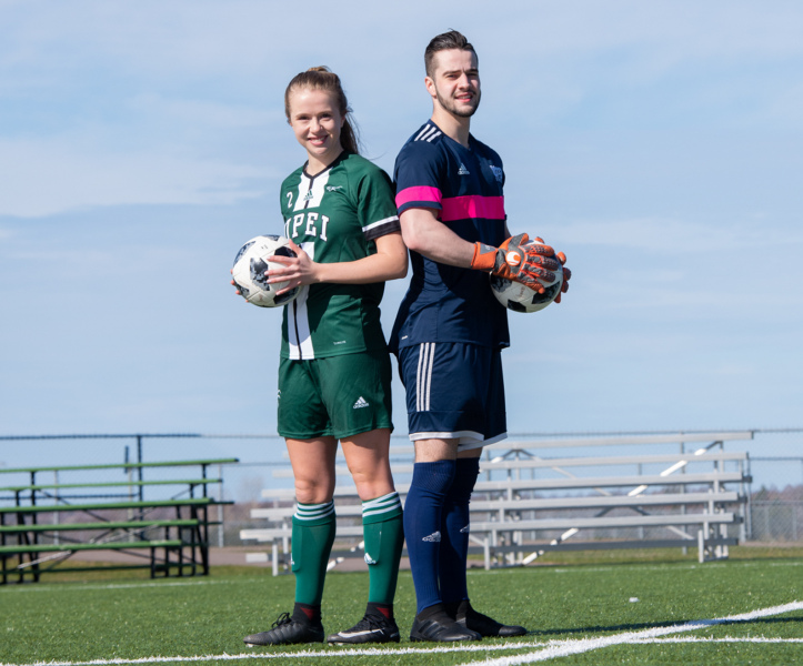 A female and a male soccer player stand back to back