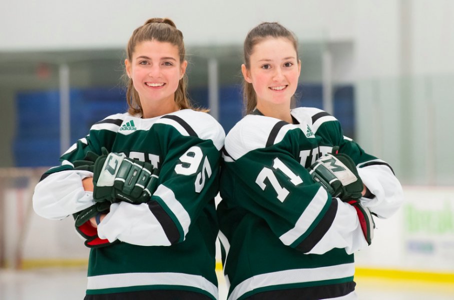 Two female hockey players stand back to back
