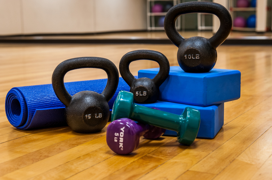 Various workout equipment sit on a wood floor: kettle bells, yoga mat, plastic weights and bricks