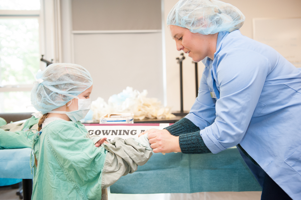 a veterinary student helps a child scrub in