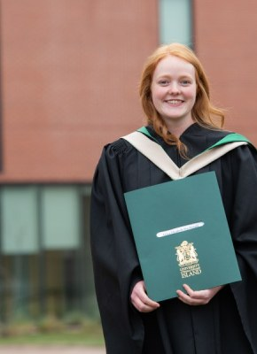 Photo of female graduate holding her degree on the UPEI campus