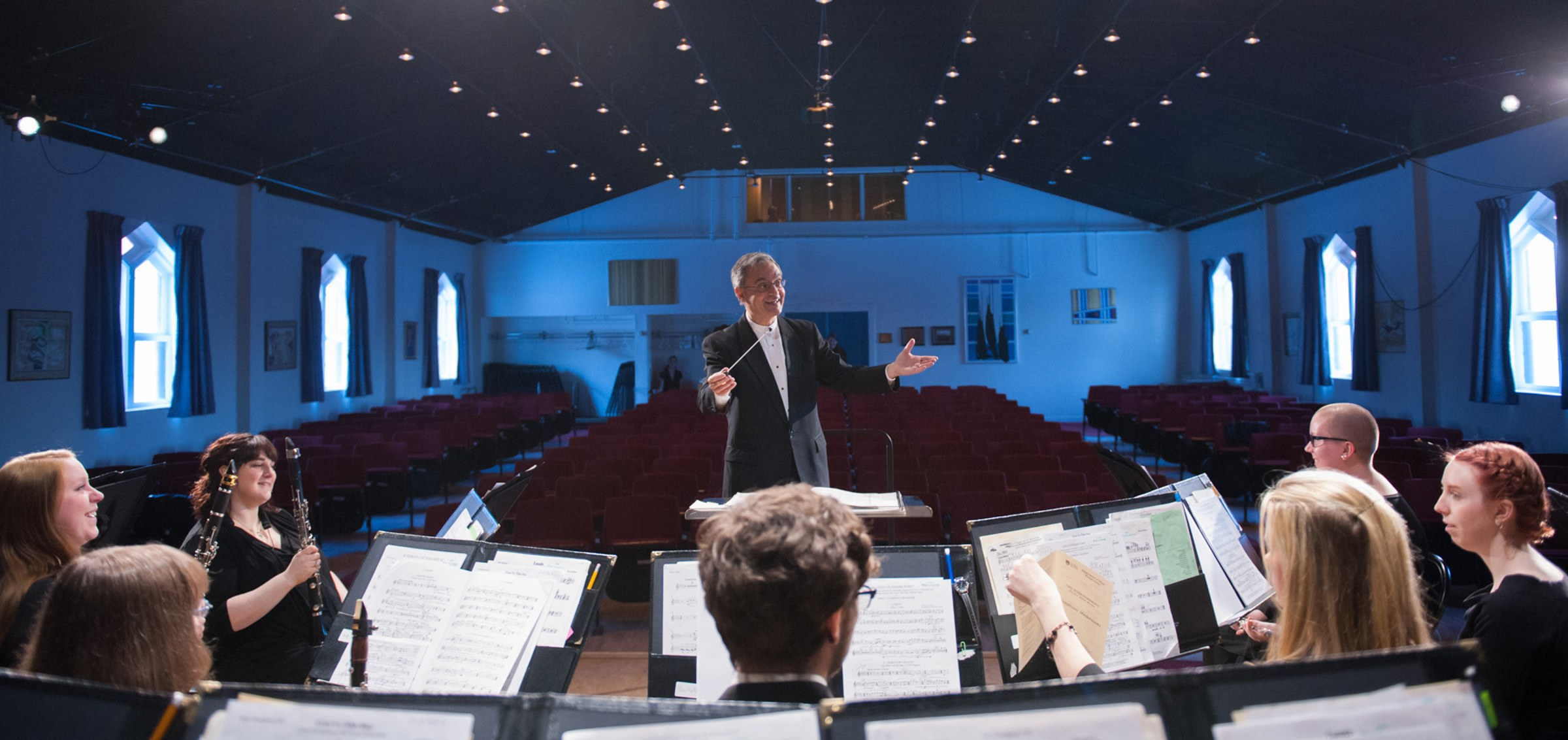 A conductor stands in front of a symphony