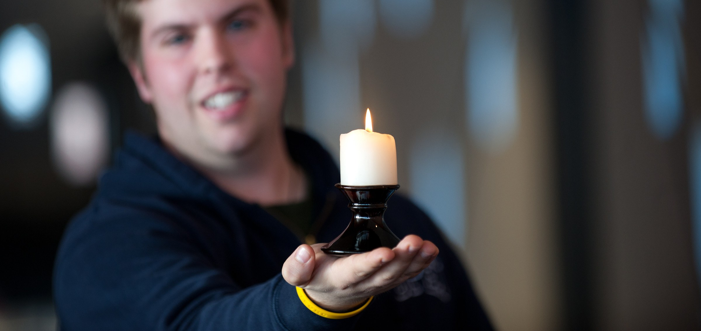 A student holds a candle