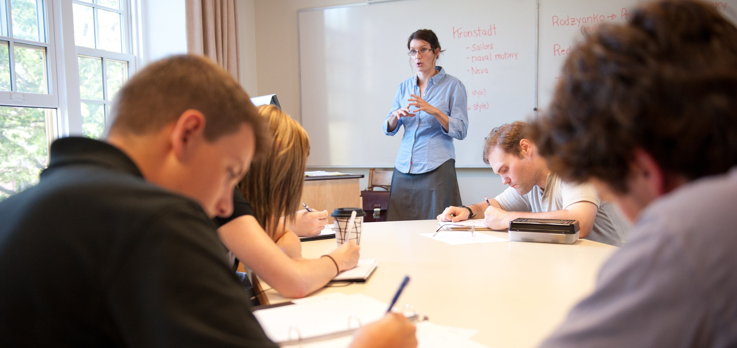 A professor speaks at the front of a classroom
