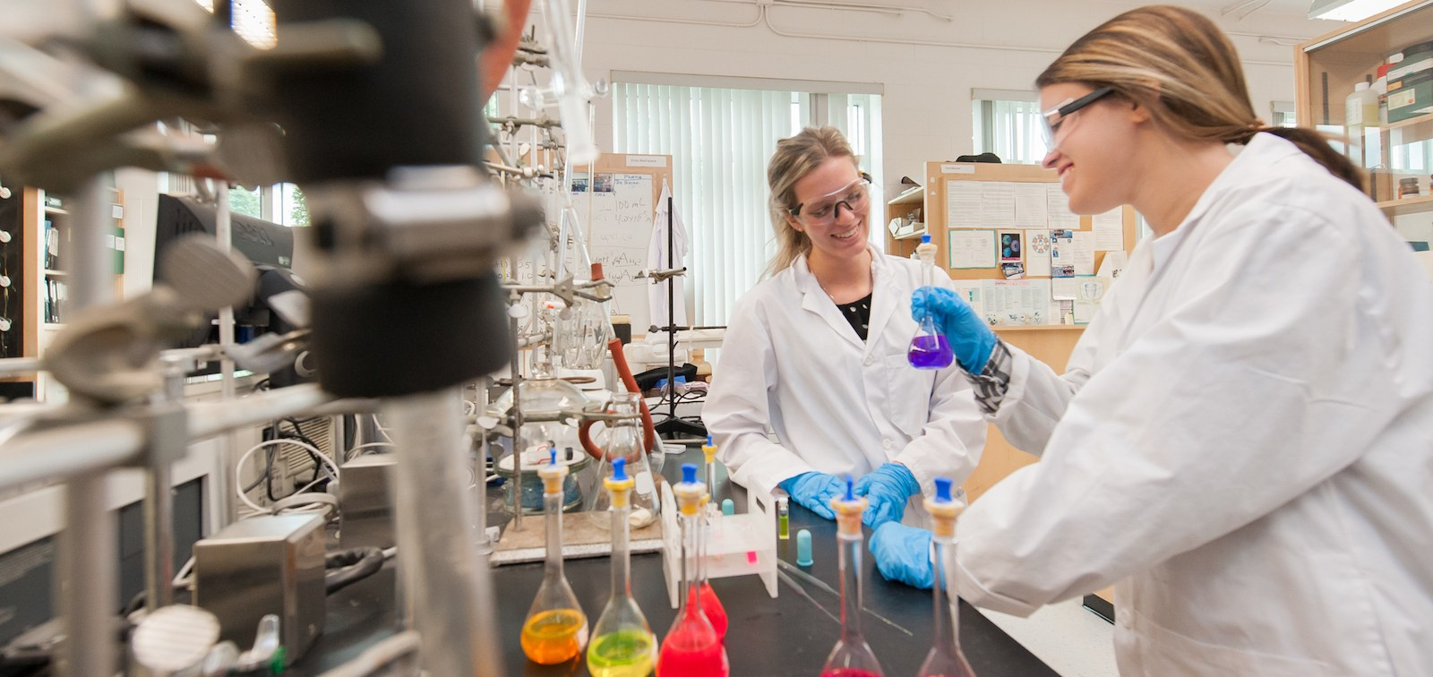 two chemistry students in laboratory with coloured flasks