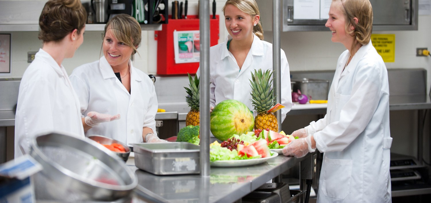 four dietitians preparing a fruit tray