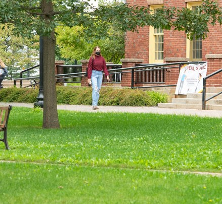 a student walks across campus in front of SDU main building
