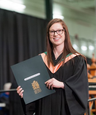 A graduate stands with her degree