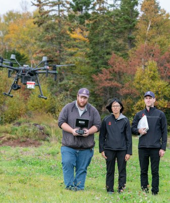climate lab workers fly a drone