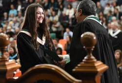A student accepts her degree