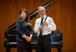 A smiling woman and a man holding a clarinet stand before a grand piano