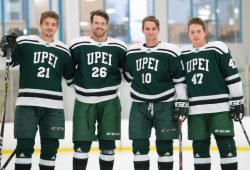 Four smiling male hockey players