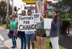 "Cheering students stand at a street corner. They hold a sign reading ""Panthers for Change."""