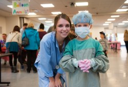 a youngster learns how to gown and glove like a veterinary surgeon