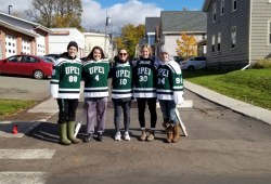 Five female hockey players stand at an intersection in Charlottetown