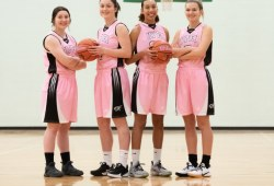 Four female basketball players in pink uniforms