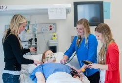 three nursing students with clinical mannequin