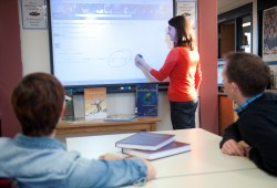 A woman writes on a smart board