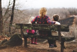 a family sitting on a park bench in fall