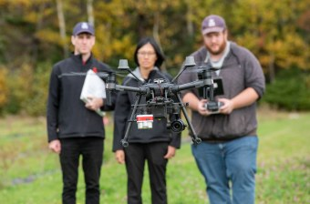 researchers look at a drone