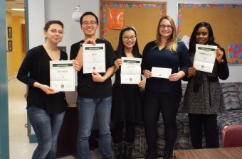 a group of five upei students holding certificates