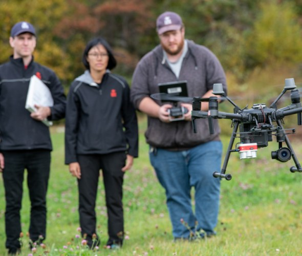 Researchers watch a drone take off