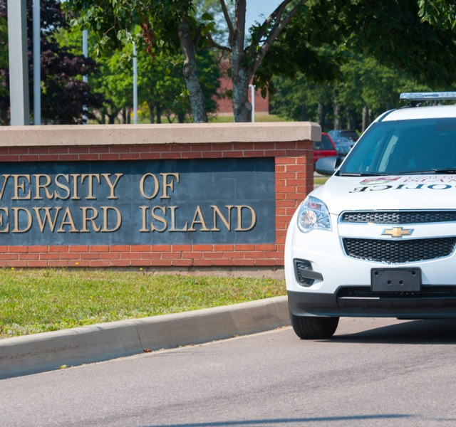 UPEI Secuity vehicle in front of univeristy main entrance sign