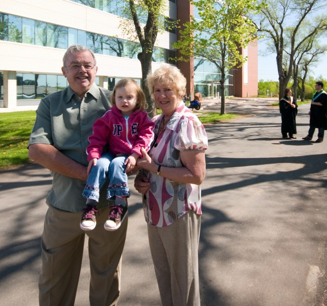Donors stand with their granddaughter on campus