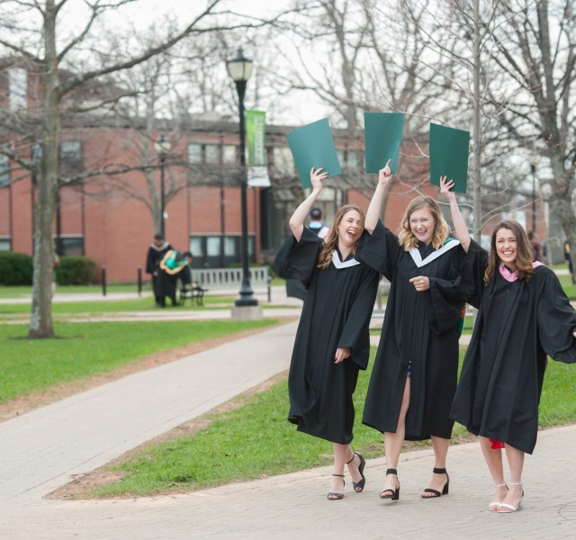 three upei graduates holding degrees in the quadrangle