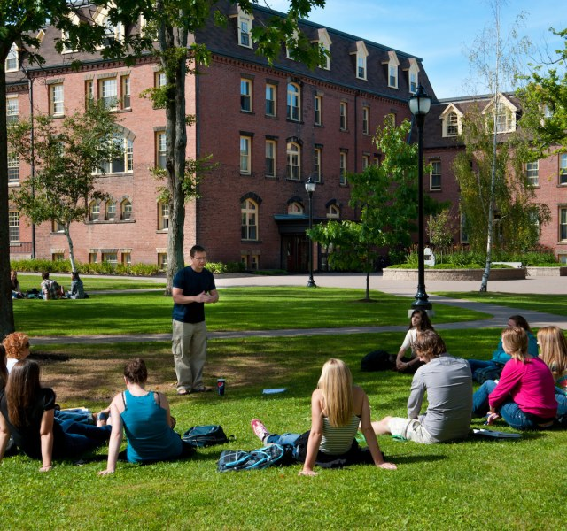 students listening to an outdoor lecture in the quad